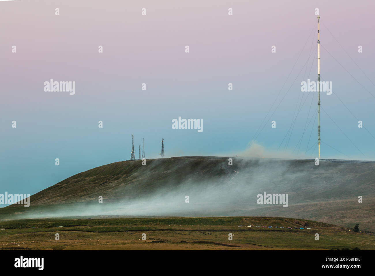 Winter Hill, Greater Manchester, UK. 28th Jun, 2018. Smoke from a grass fire rolls down the moors beneath the Winter Hill transmission masts. Credit: Jason Smalley Photography/Alamy Live News Stock Photo