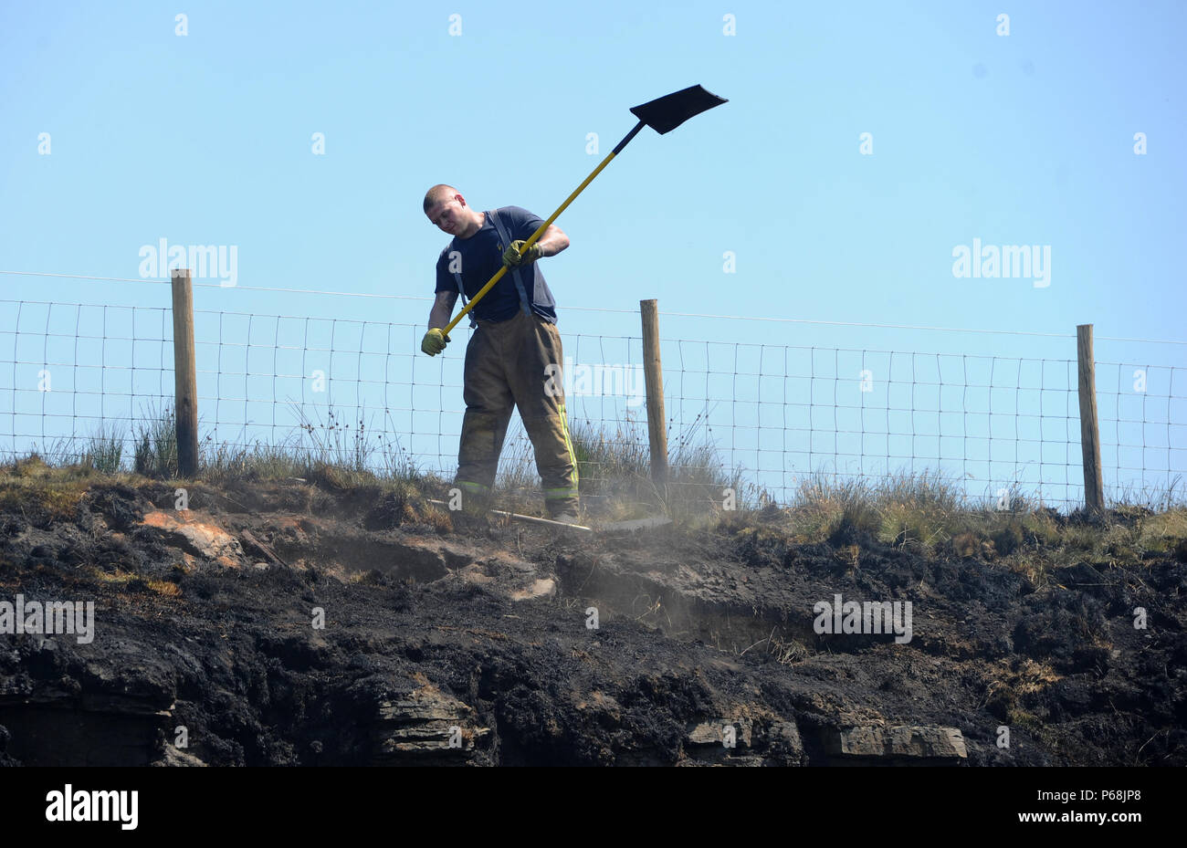 Winter Hill near Bolton, Lancashire, UK. 29th June, 2018. More than 80 firefighters from Lancashire, Merseyside and Cumbria continue to tackle a huge moorland fire for a second day on Winter Hill near Bolton, Lancashire. A 22 year old man from Bolton has been arrested on suspicion of arson with intent to endanger life. Picture by Credit: Paul Heyes/Alamy Live News - Stock Image