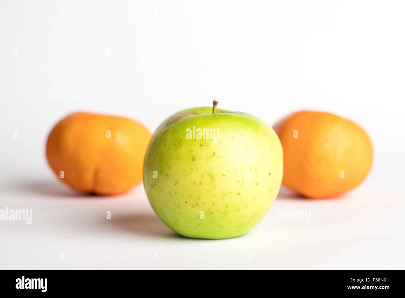 One green juicy apple on centre with small spots with 2 mandarins below on a white background with a soft shadow - Stock Image