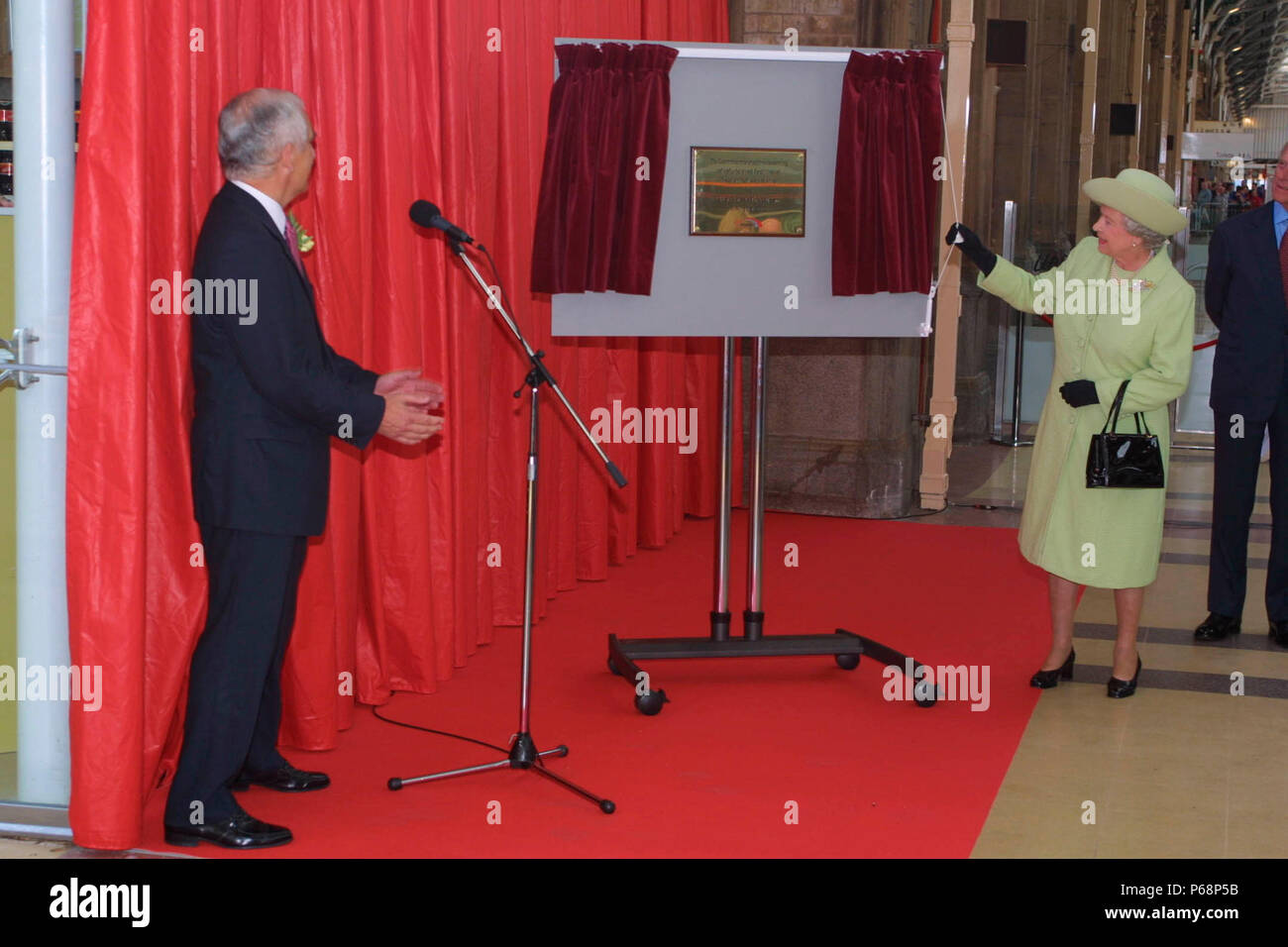 The Queen reveals a plaque at Preston station whilst Chris Green looks on. 2003. - Stock Image