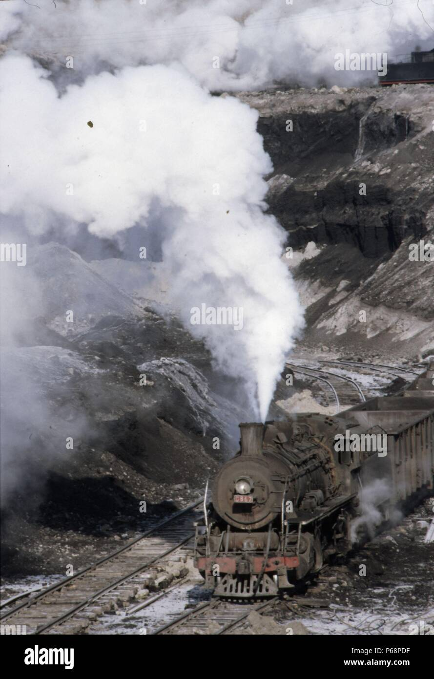 The vast opencast coal mine at Manzhouli in Inner Mongolia on the Russian border in north east China. The coal and spoil is bought out by steam trains Stock Photo