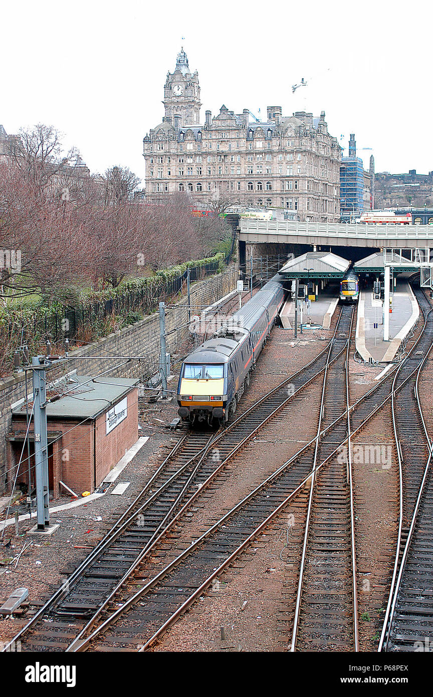 The western end of Edinburgh Waverley sees the arrival of a Glasgow Central - Kings Cross service under the shadow of the station's North British Hote - Stock Image