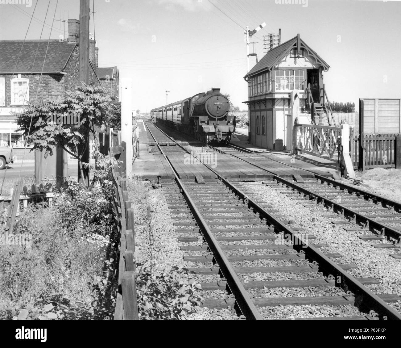 Thompson Class B1 at the head of a passenger train passes a signal box and level crossing at an unknown location in the east of England. C 1960 - Stock Image