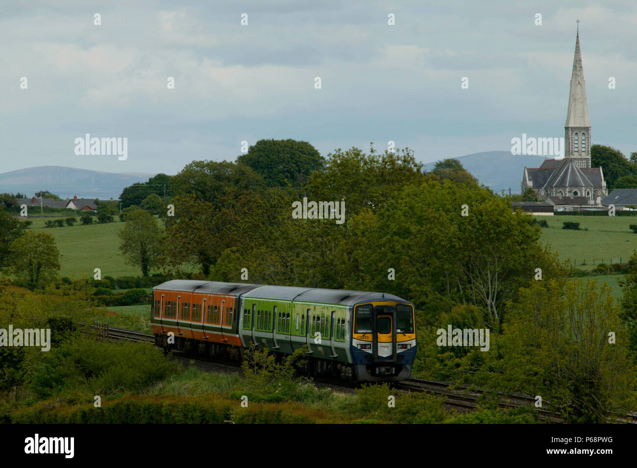 Two CIE DMUs in tandem head eastward past the white abbey at Kildare on Sunday 25th May 2003. - Stock Image