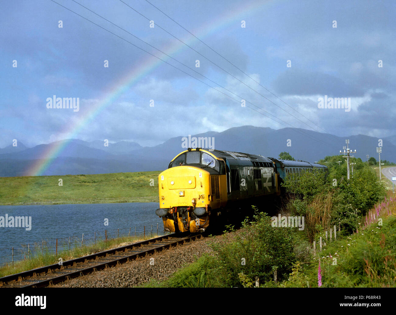West Highland Line. A rainbow welcomes 37424 out of the rain as it skirts Loch Eil with the 06:50 ex Mallaig for Fort William. 08.07.1986. - Stock Image