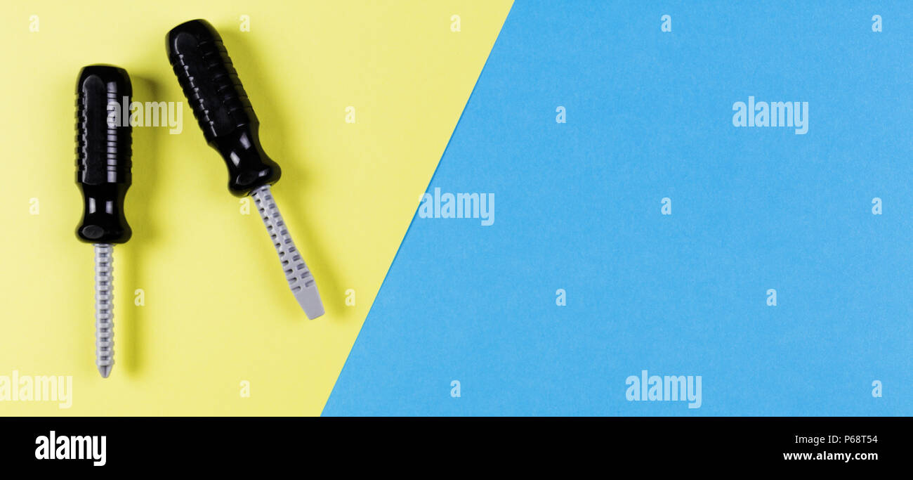 Toys background. Kids construction toys tools on blue and yellow background. Top view - Stock Image