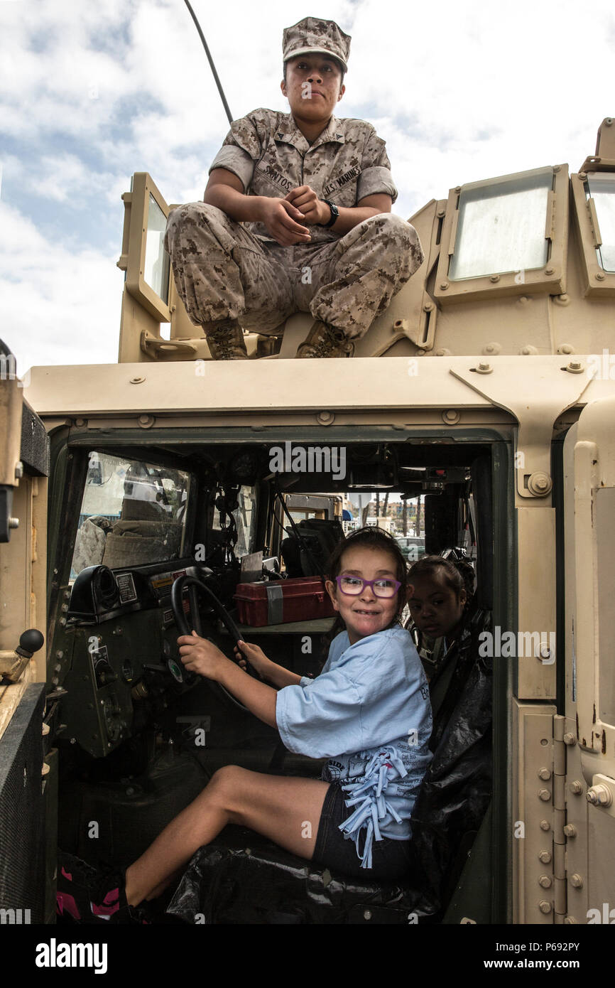 "OCEANSIDE, Calif. – Lance Cpl. Sharon Santos, top, poses for a photo with JoJo, age 7, during the annual Beach Fun Day May 20, 2016. During the event, Marines gave special needs children an inside look at some of the equipment they use in the military. ""They were just so excited to get behind the wheel and get up on the turret. I could tell they had a lot of fun today,"" said Santos, a motor transportation operator with 1st Marine Logistics Group. (U.S. Marine Corps photo by Sgt. Emmanuel Ramos/Released) - Stock Image"