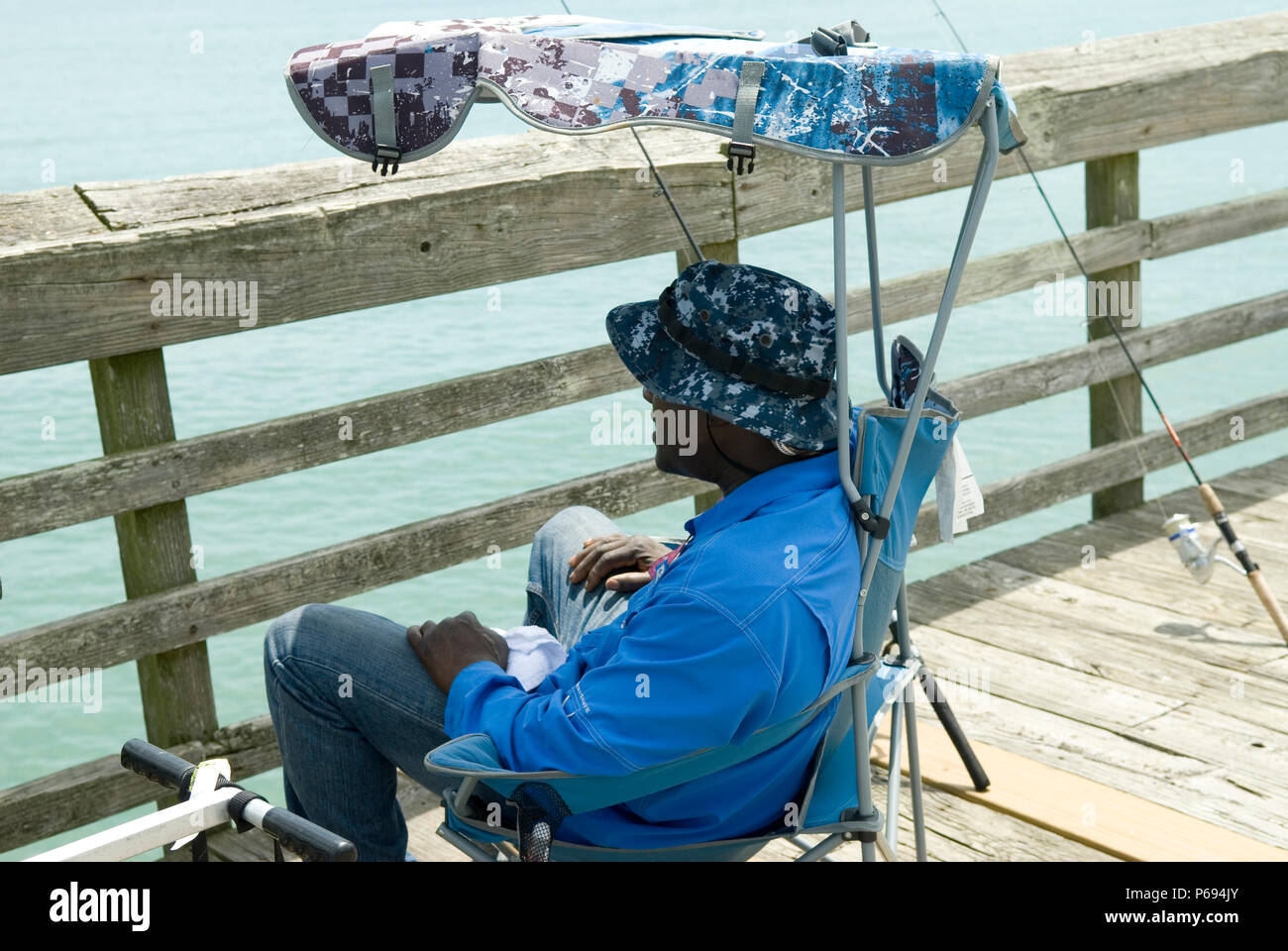 Man relaxes in chair on pier at Myrtle Beach State Park, SC, USA. Stock Photo