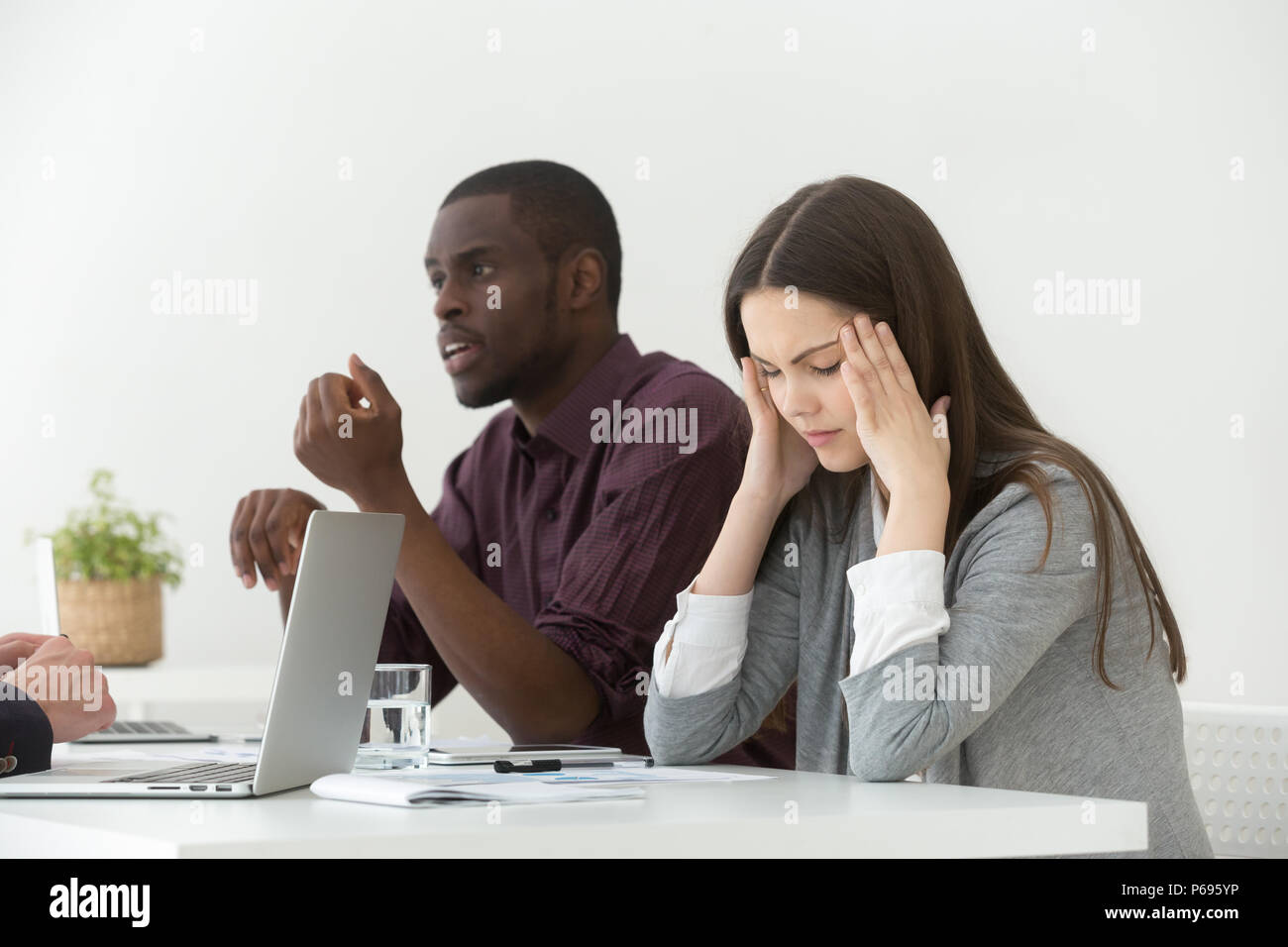 Stressed female suffering from headache during business meeting - Stock Image