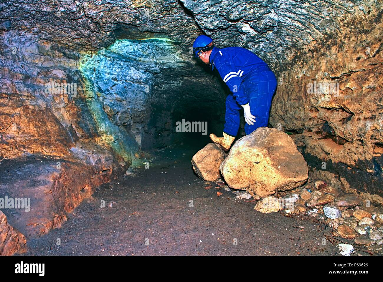 Man works in mystical ancient long tunnel from orange sandstone walls, city underground. Interiors of castle catacombs, view through the stone tunnel - Stock Image