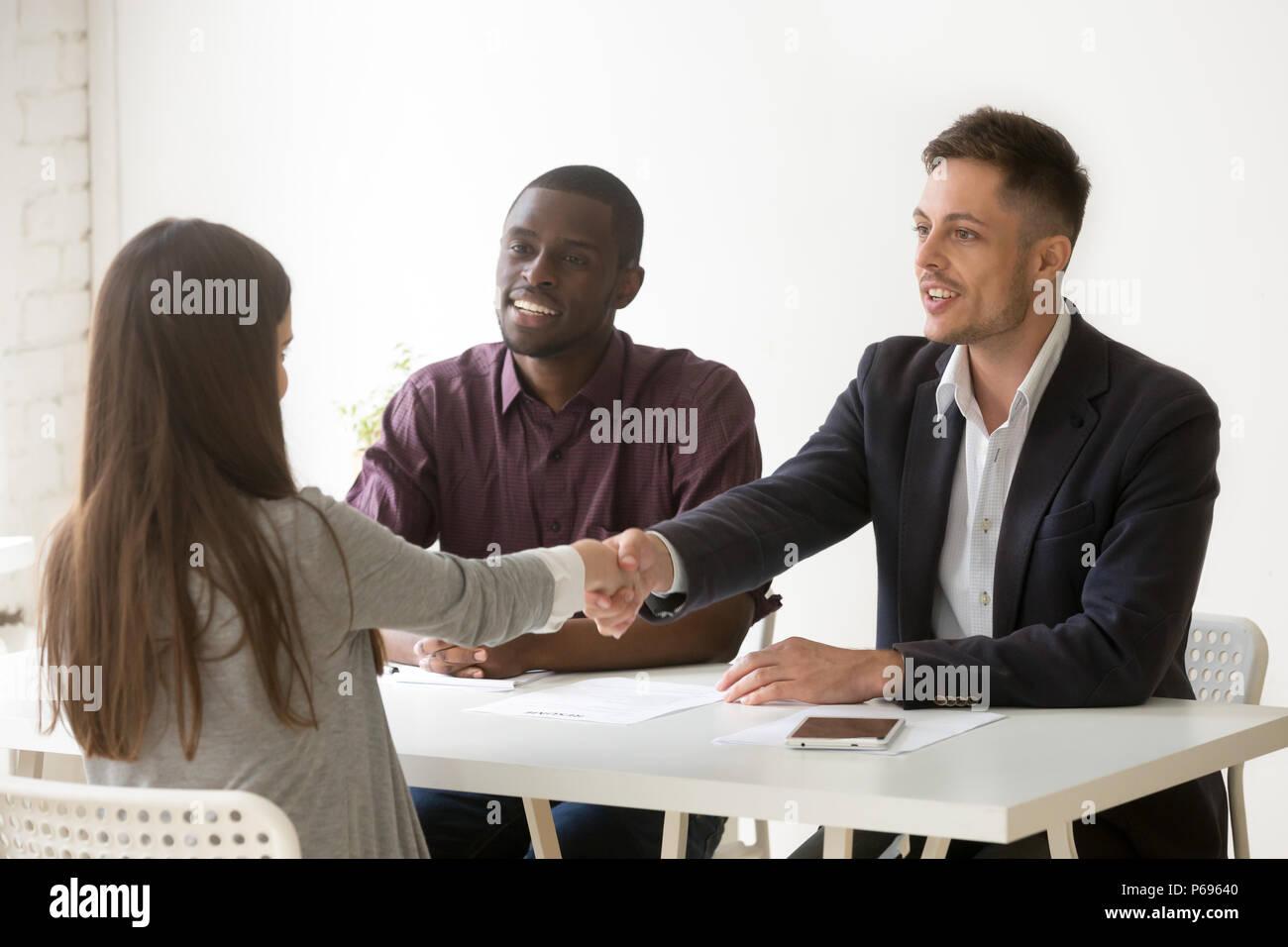 Multiethnic employers greeting female job candidate with handsha - Stock Image