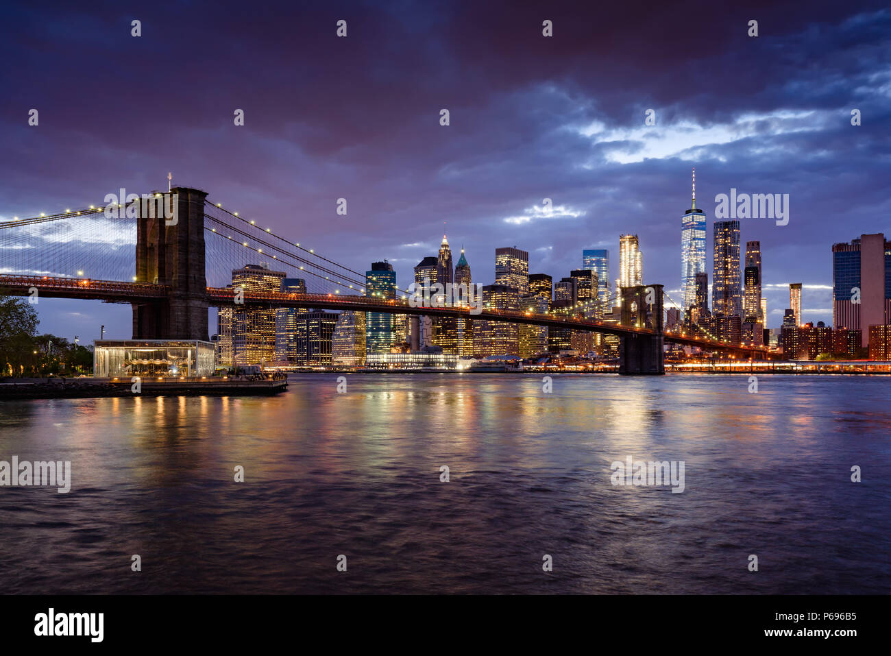 Brooklyn Bridge and illuminated Lower Manhattan skyscrapers at dusk with the East River. Manhattan, New York City, USA - Stock Image