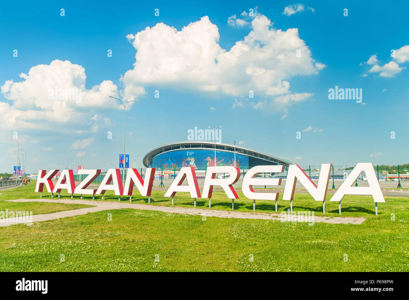KAZAN, RUSSIA - 25 JUNE, 2018: View of Kazan Arena stadium with big sign on green grass in foreground and stadium building with big screen in backgrou Stock Photo