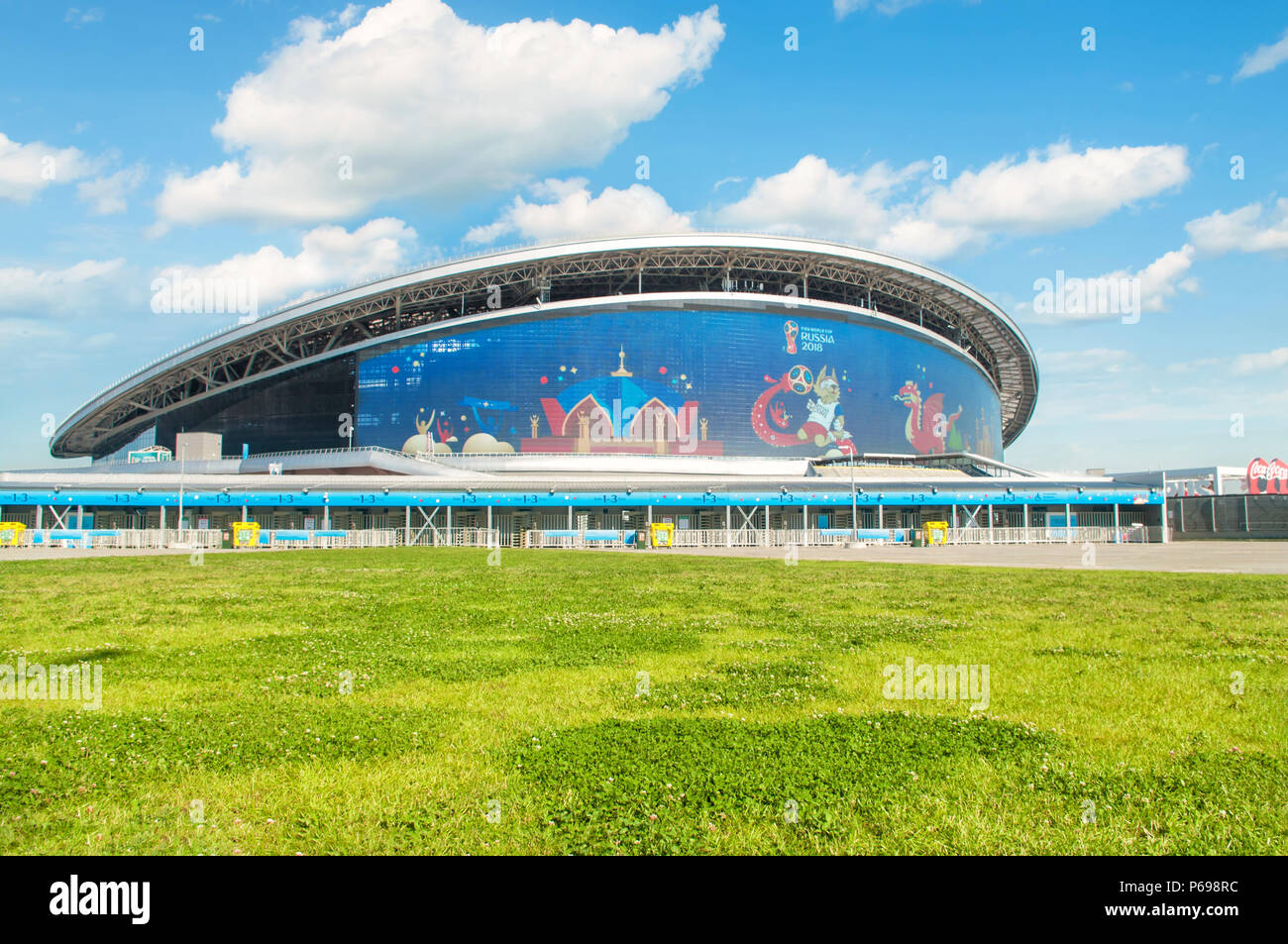 KAZAN, RUSSIA - 25 JUNE, 2018: Kazan Arena stadium with green grass in foreground and FIFA 2018 symbol Zabivaka on big screen. Stock Photo