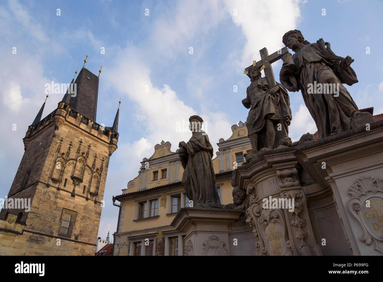 St. Cosmas and Damian statue on the Charles Bridge. Mostecka/Lesser Bridge tower in Mala Strana, Prague, Czech Republic - Stock Image