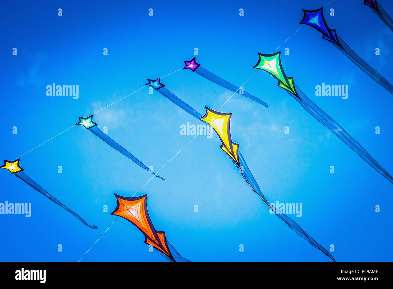 Close up image of brightly colored flying kites against a summer blue sky - Stock Image