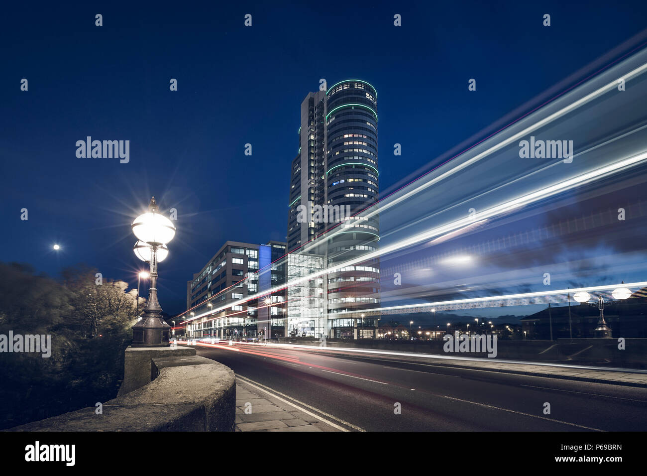 Dusk in Leeds, UK. Traffic leaves light trails with Bridge water place in the background. - Stock Image