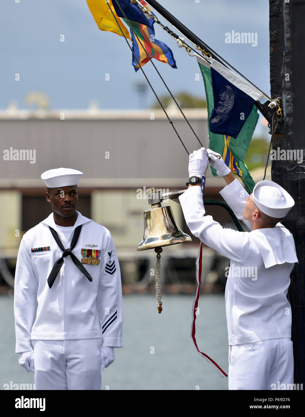 160530-N-LY160-379 JOINT BASE PEARL HARBOR-HICKAM, Hawaii (May 30, 2016) Sailors assigned to Los Angeles-class fast-attack submarine USS City of Corpus Christi (SSN 705) strike the commissioning pennant during a Memorial Day decommissioning ceremony at Joint Base Pearl Harbor-Hickam. City of Corpus Christi concluded 33 years of service as the second U.S. warship to be named after Corpus Christi, Texas. (U.S. Navy photo by Mass Communication Specialist 2nd Class Michael H. Lee) - Stock Image