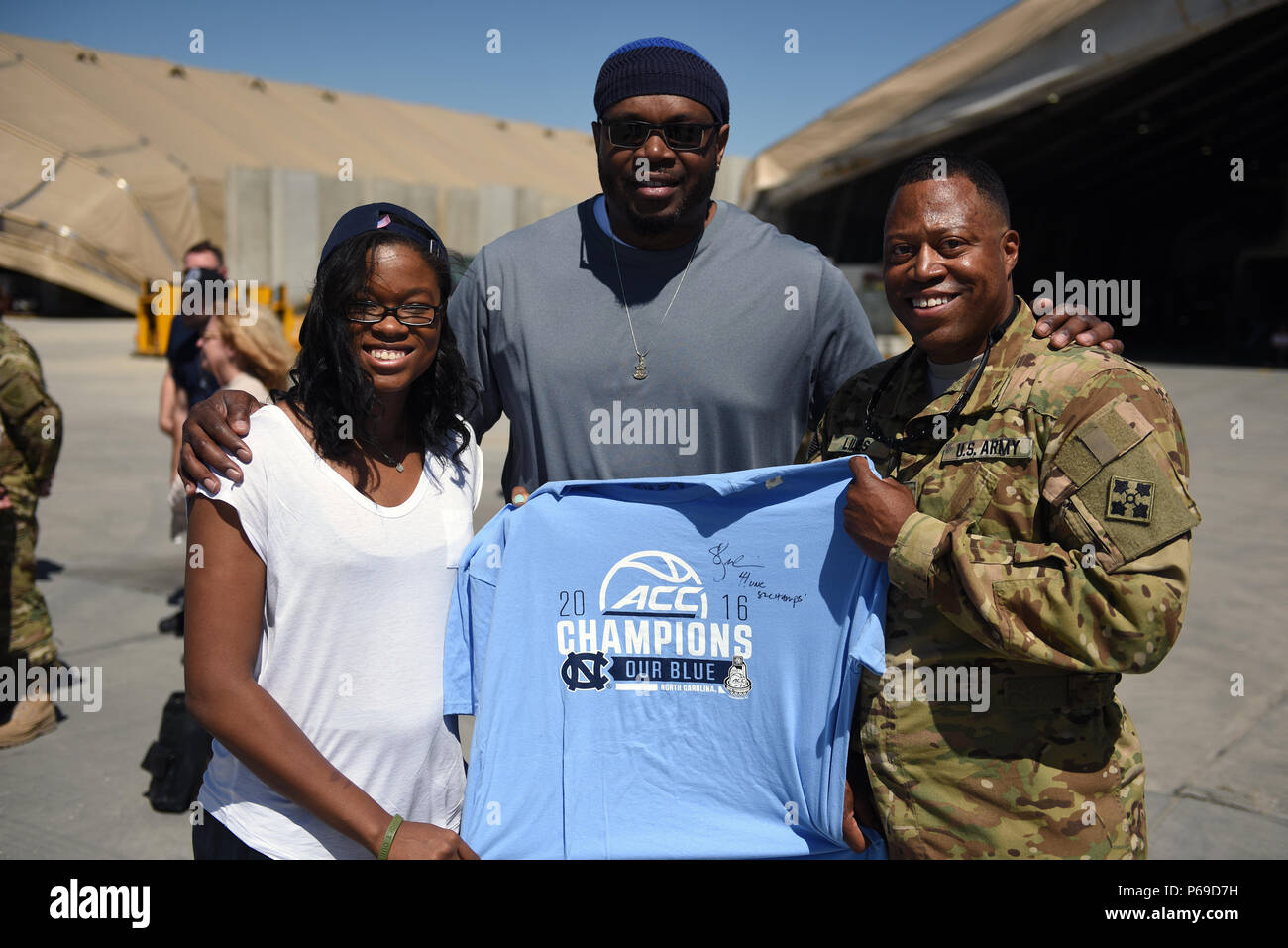Former NBA player Sam Perkins, who played for the Univesity of North Carolina at Chapel Hill during his college career, poses with a Tar Heel fan and daughter China Perkins in Afghanistan as Army Gen. Frank Grass, chief, National Guard Bureau, leads the first-ever National Guard USO Tour, May 19, 2016. (U.S. Army National Guard photo by Sgt. 1st Class Jim Greenhill) (Released) Stock Photo