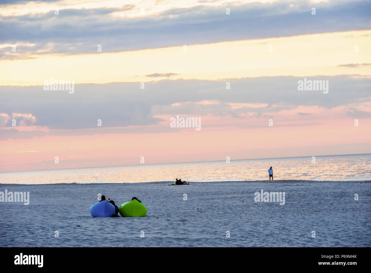 two people relaxing on mattresses during the sunset by the sea - Stock Image