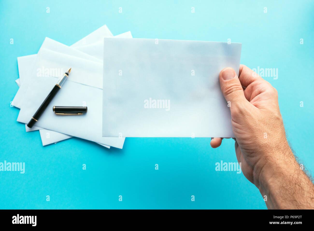 Hand holding blank white envelope, mock up image for communication and correspondence themes - Stock Image