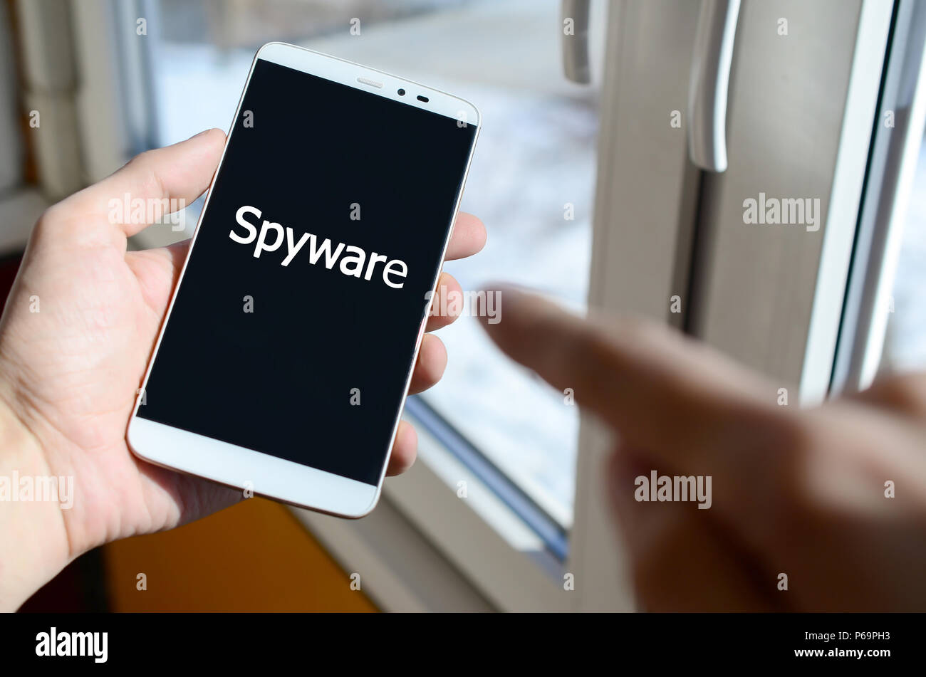 A person sees a white inscription on a black smartphone display that holds in his hand. Spyware . - Stock Image