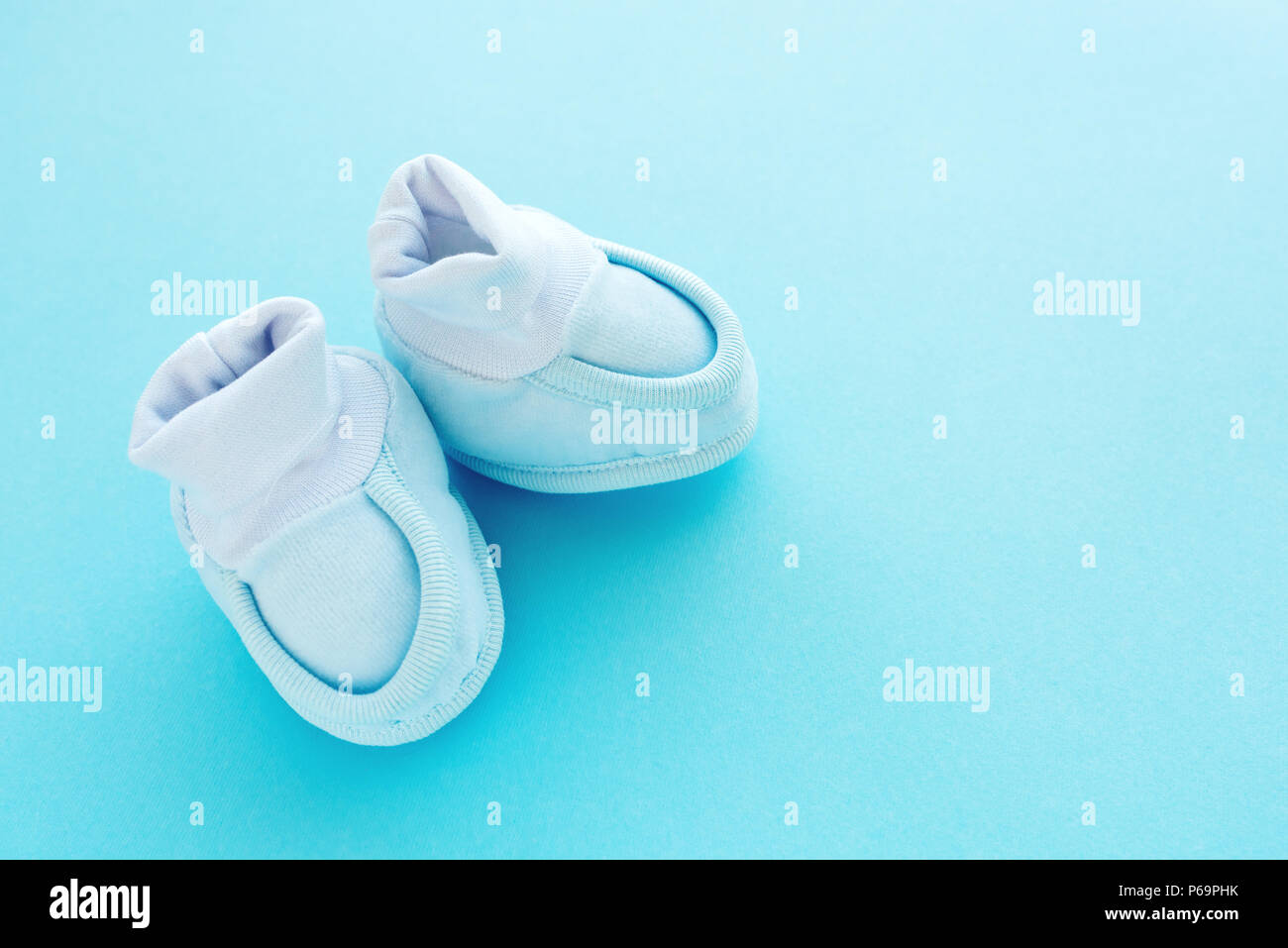 newborn baby boy cotton shoes on pastel blue background stock photo