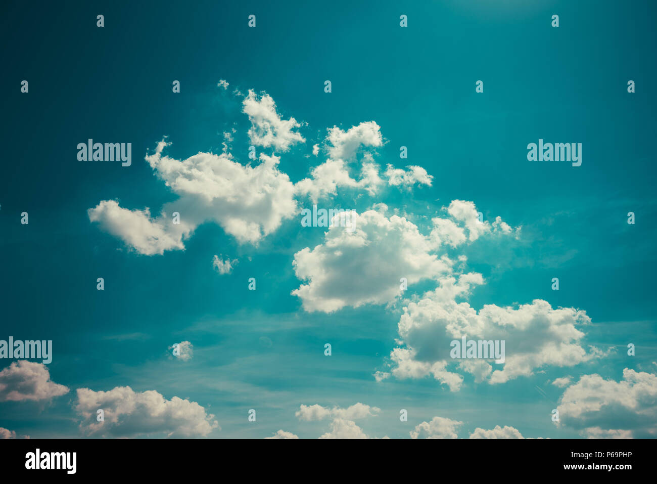Perfect idyllic blue summer sky with white fluffy clouds and sunlight as nice weather background - Stock Image