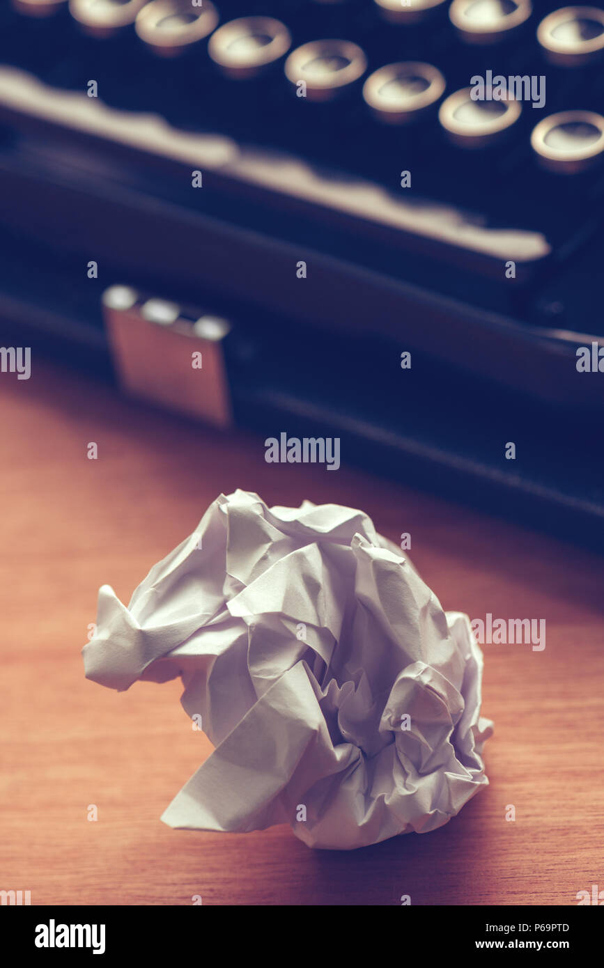 Writer's block concept with typewriter and crumpled paper on work desk - Stock Image