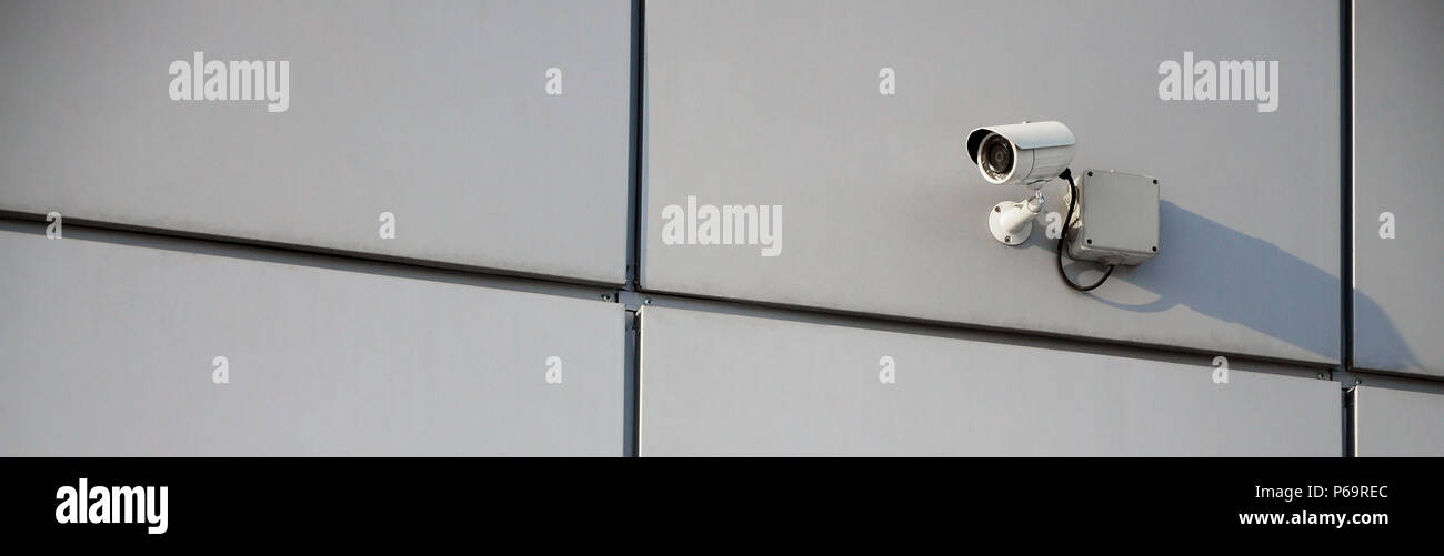 White surveillance camera built into the metal wall of the office building . - Stock Image