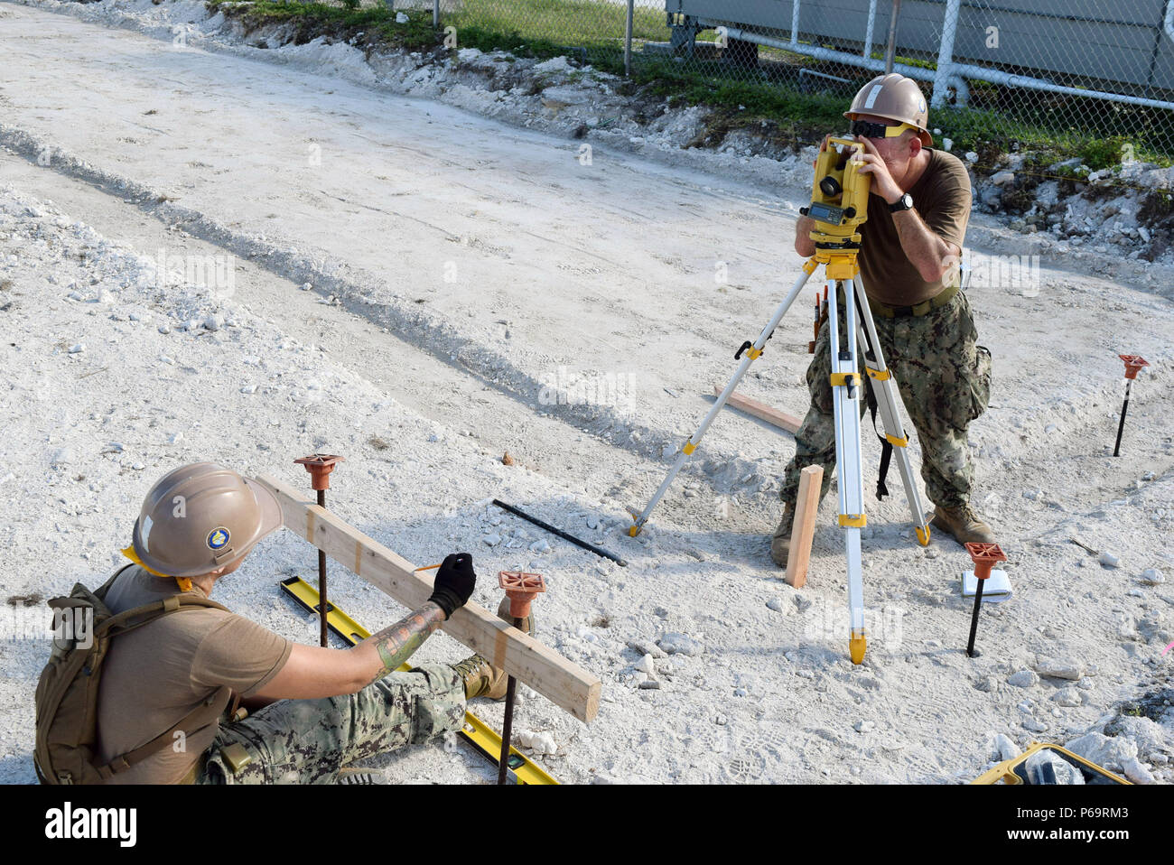 160506-N-OA861-004  DIEGO GARCIA (May 6, 2016) - Builder 1st Class Charles Durnell (right), assigned to Naval Mobile Construction Battalion (NMCB) 4, shoots measurements through a Transit Level with Steelworker 2nd Class Kaylynn Barajas (left) in Diego Garcia, May 6.  Using the transit level on the batter boards will provide the exact corner locations for placing and squaring off the formwork for the Gas Cylinder storage concrete pad.  (U.S. Navy photo by Builder 3rd Class Xavier Spencer/Released) - Stock Image