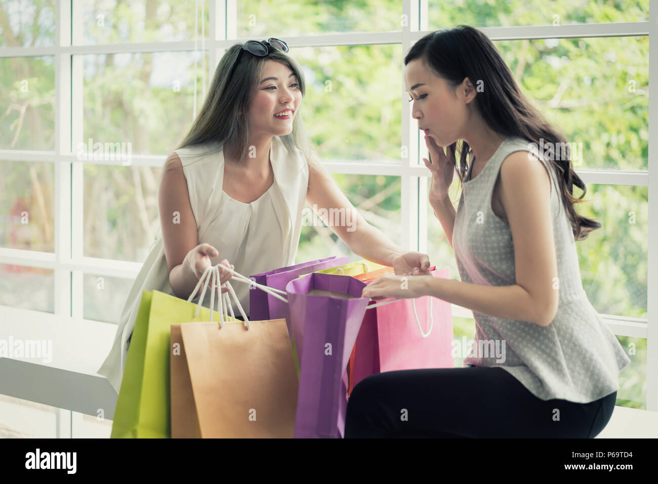 e40f977c1b Young Asian woman in shopping mall hold shopping bag and looking in bag and  surprise with wonderful beauty fashion accessories, clothes, makeup in pac