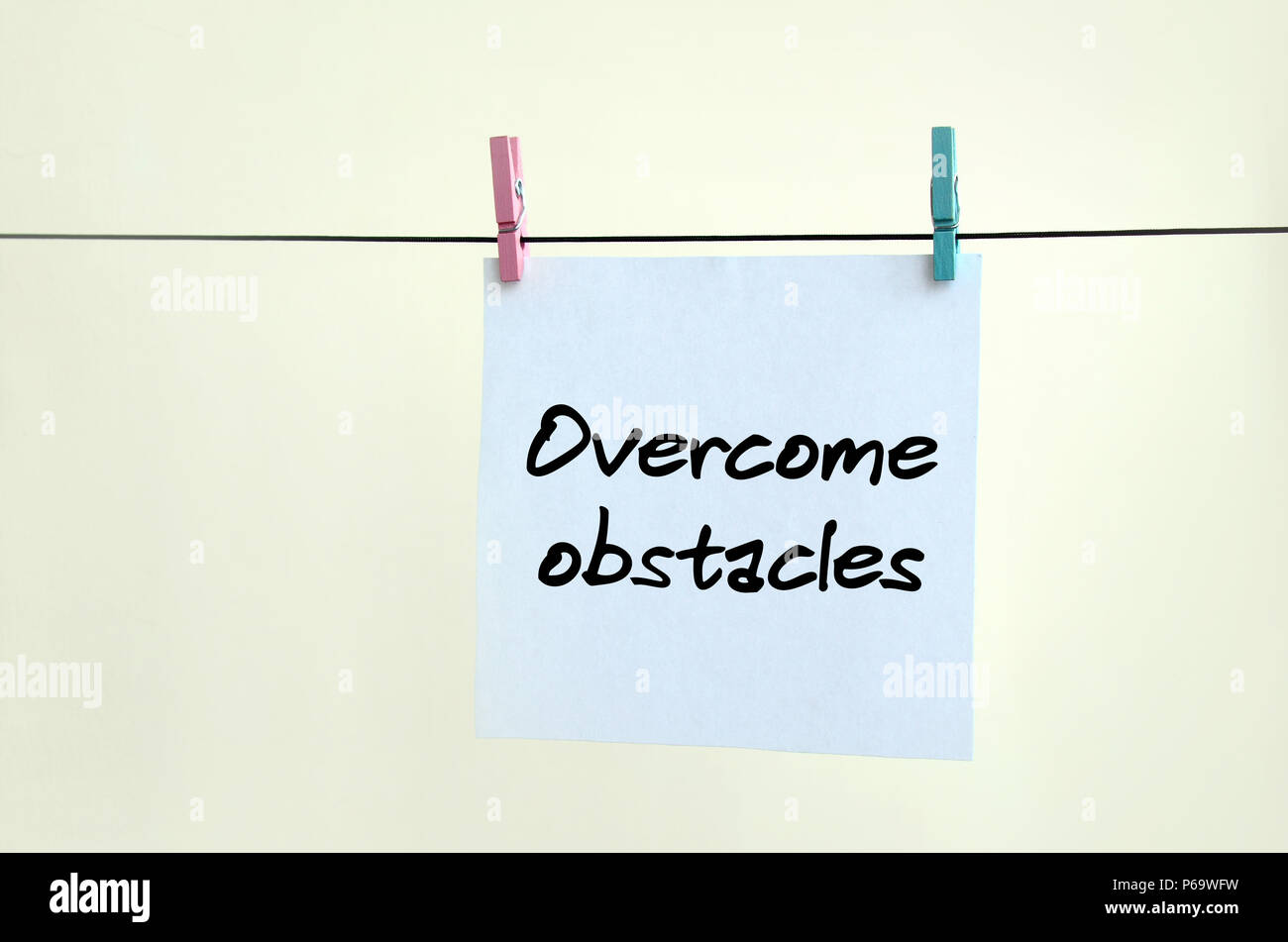 Overcome obstacles. Note is written on a white sticker that hangs with a clothespin on a rope on a background of beige wall . - Stock Image