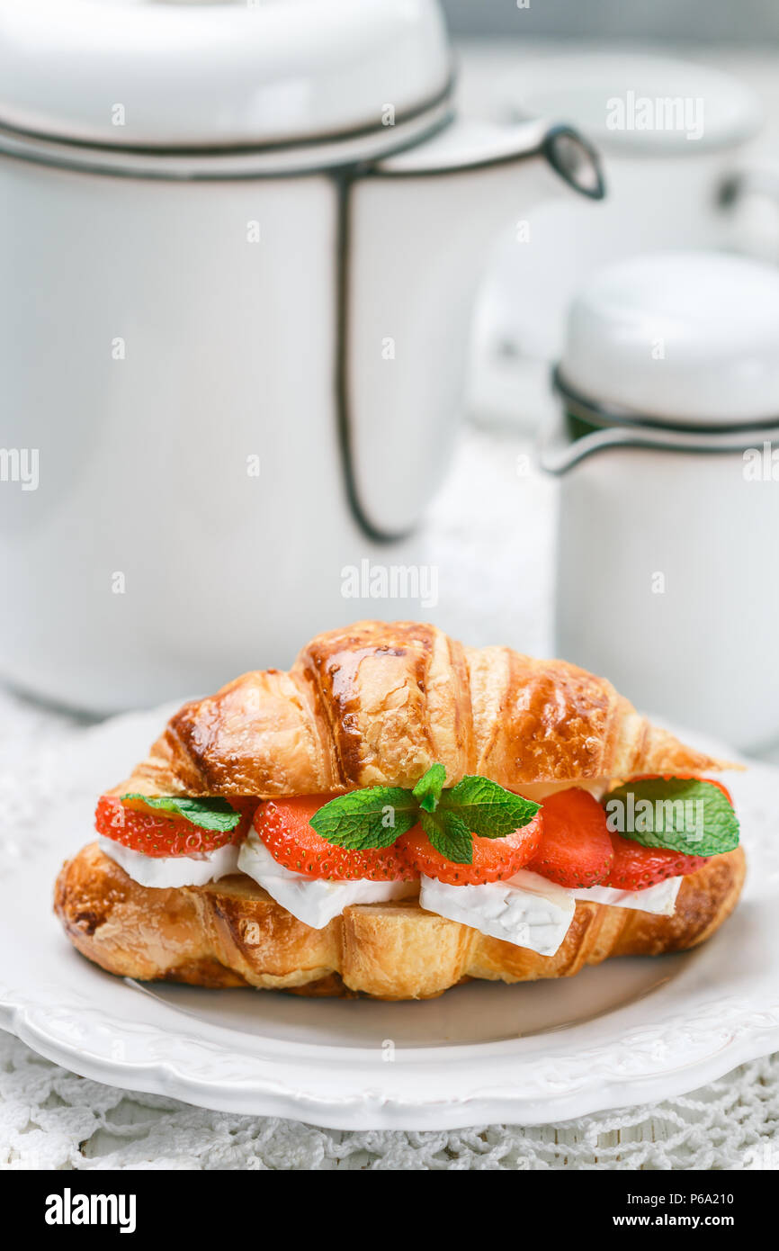 Croissant with strawberries, brie cheese or Camambert and mint. Delicious gourmet Breakfast. Selective focus - Stock Image