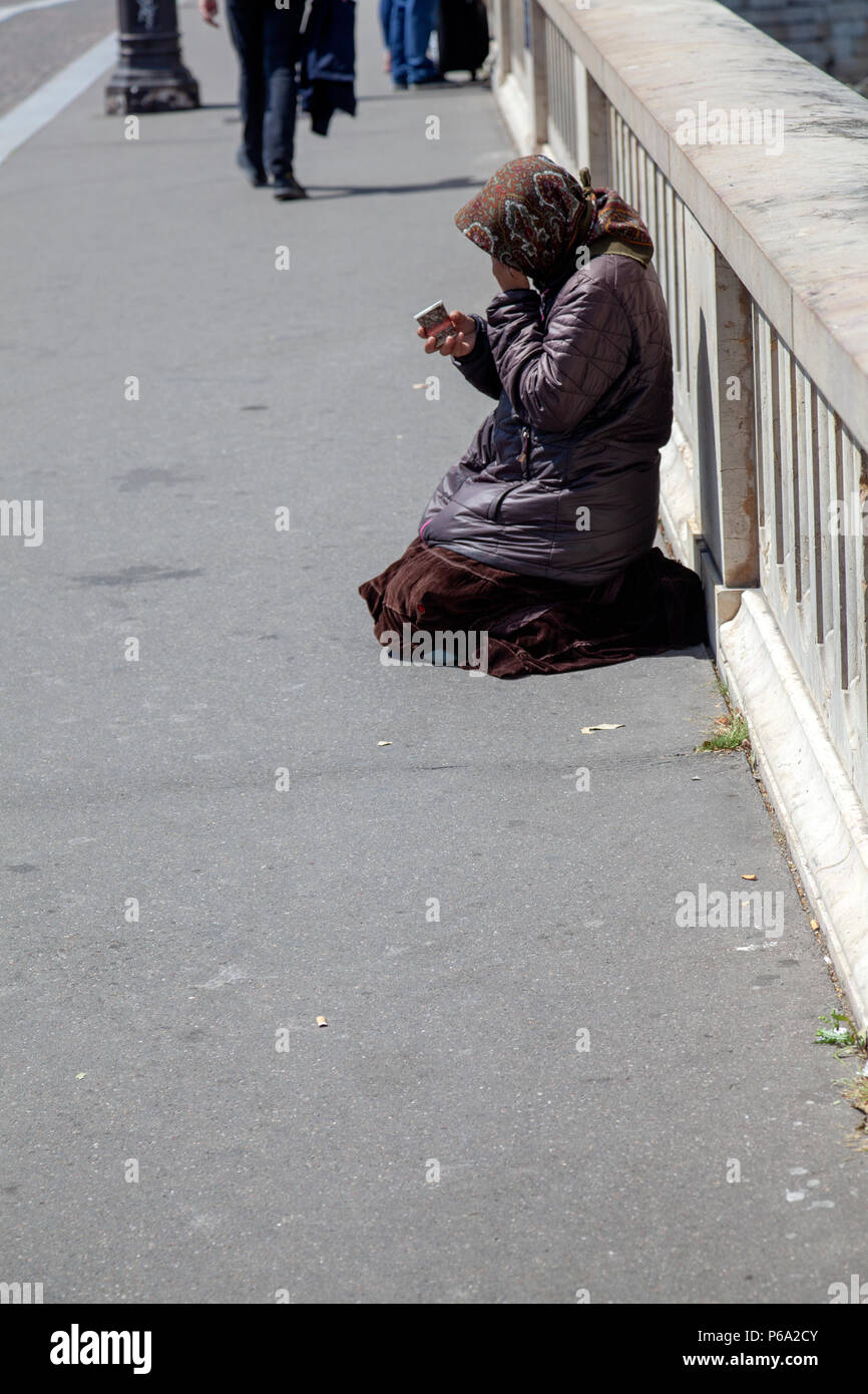 Woman Begging on Pont Louis Philippe - Bridge over River Seine in Paris, France - Stock Image