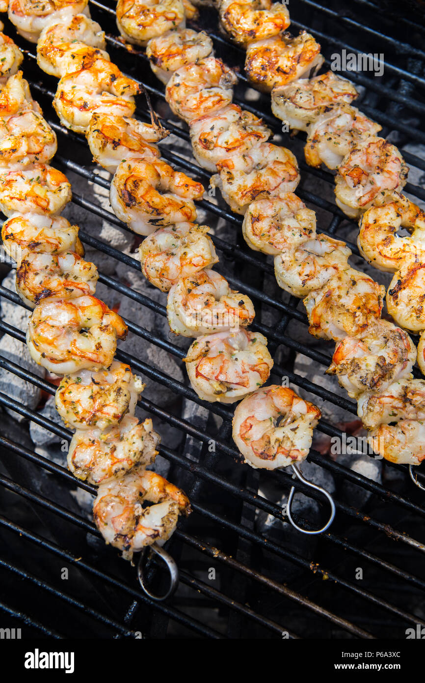 Shrimp skewered and cooking on a outdoor charcoal barbecue in southern California USA - Stock Image