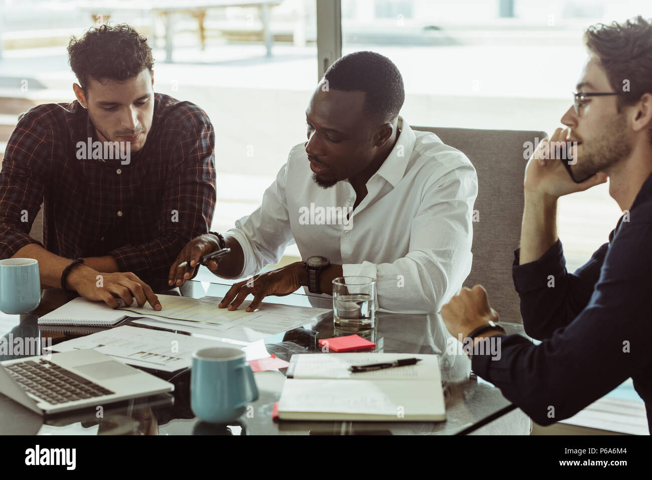 Businessmen discussing work sitting at conference table in office. Two men discussing work while another man is talking on mobile phone. - Stock Image