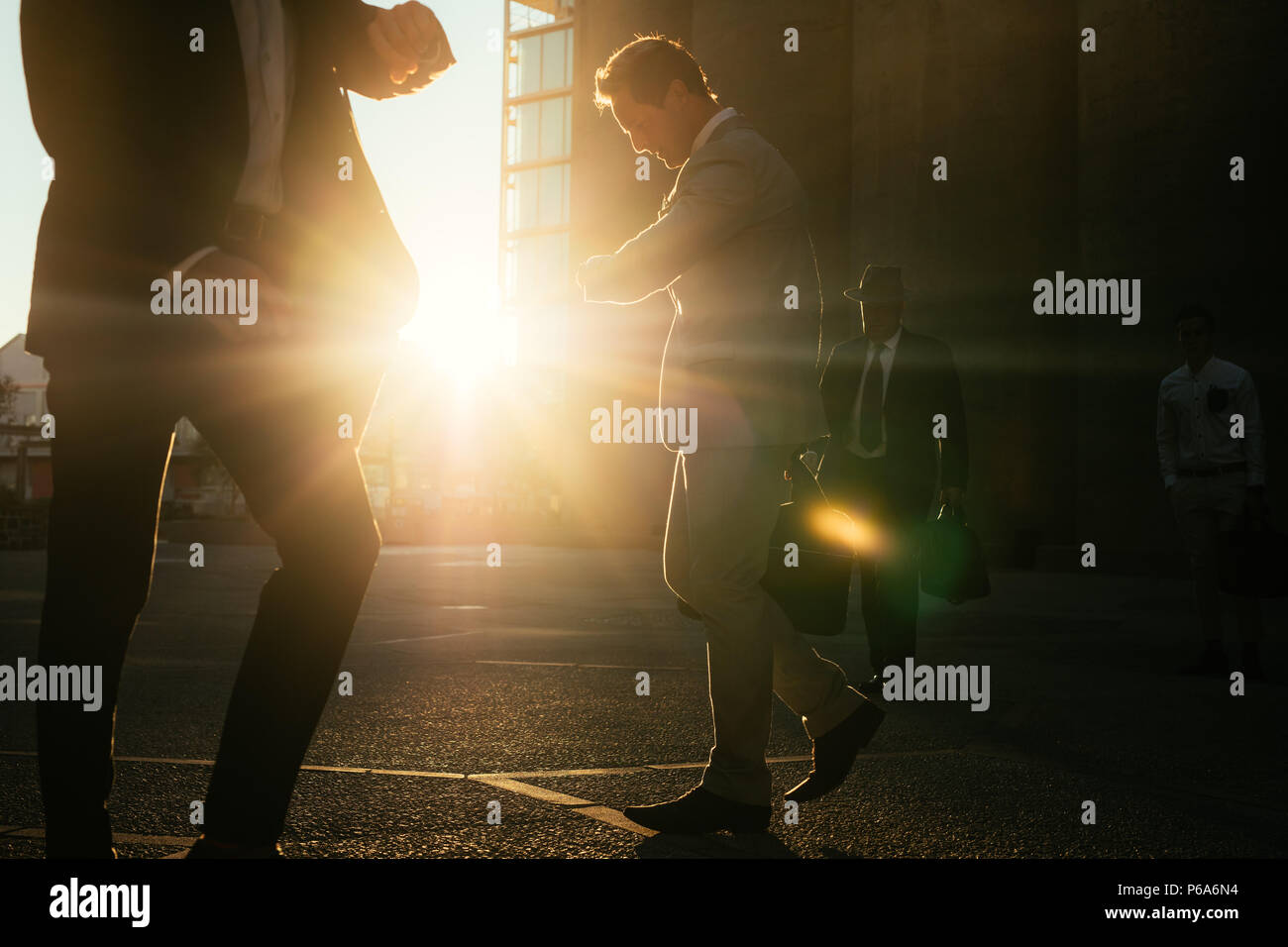 Men commuting to office early in the morning carrying office bags looking at their wrist watch. Businessmen in hurry to reach office walking on city s - Stock Image