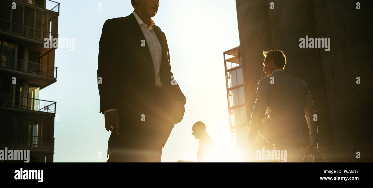 Men in formal clothes commuting to office early in the morning carrying office bags. Businessmen in hurry to reach office walking on city street with  - Stock Image