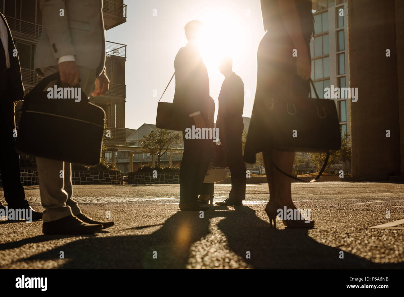 Men and woman in formal clothes commuting to office in the morning carrying office bags. Office going people standing on a busy street with sun flare  - Stock Image