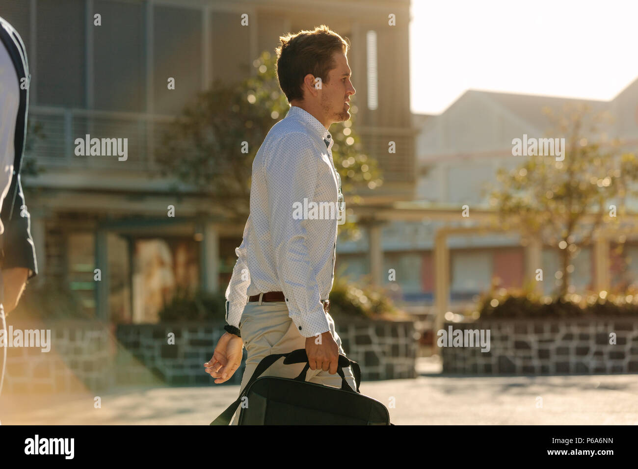 Man commuting to office carrying his office bag. Man in formal clothes walking on street to office in the morning with sun flare in the background. - Stock Image