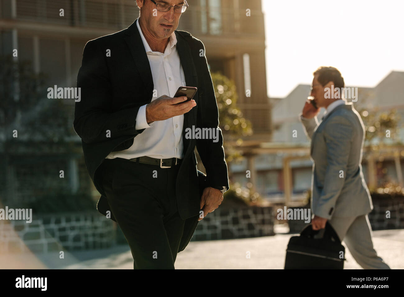 Businessman looking at his mobile phone while walking on street to office. Busy office going people carrying office bag and using mobile phone. - Stock Image