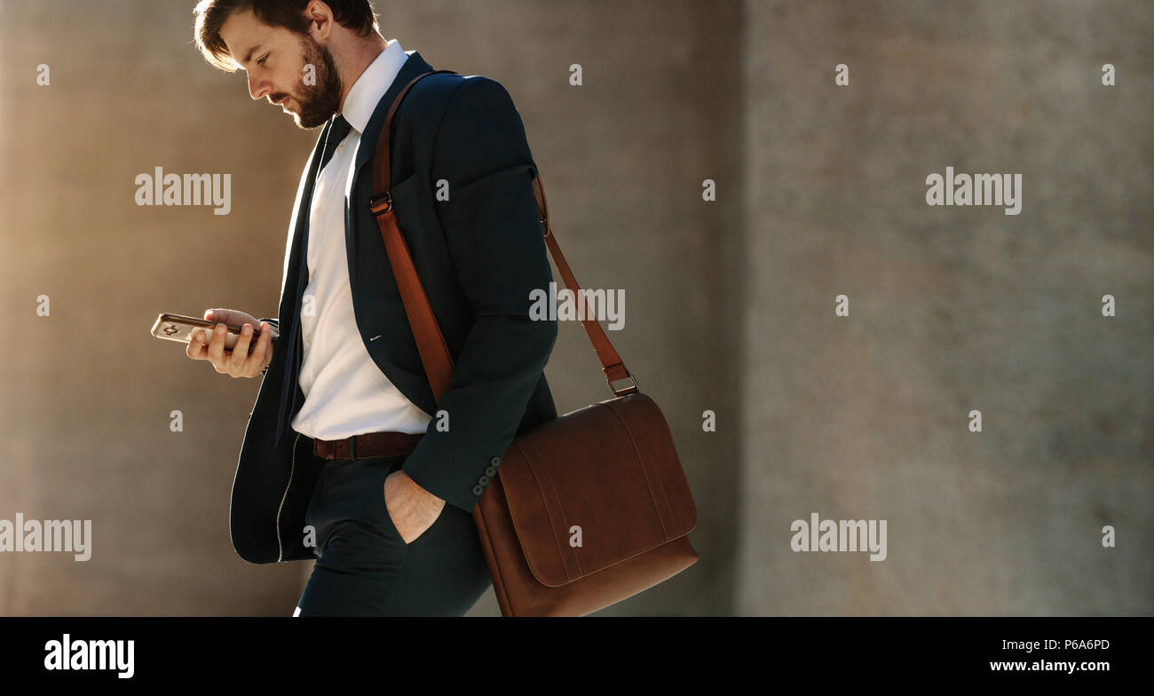 Businessman looking at his mobile phone while walking on street to office. Busy office going man commuting to office carrying his office bag and using - Stock Image
