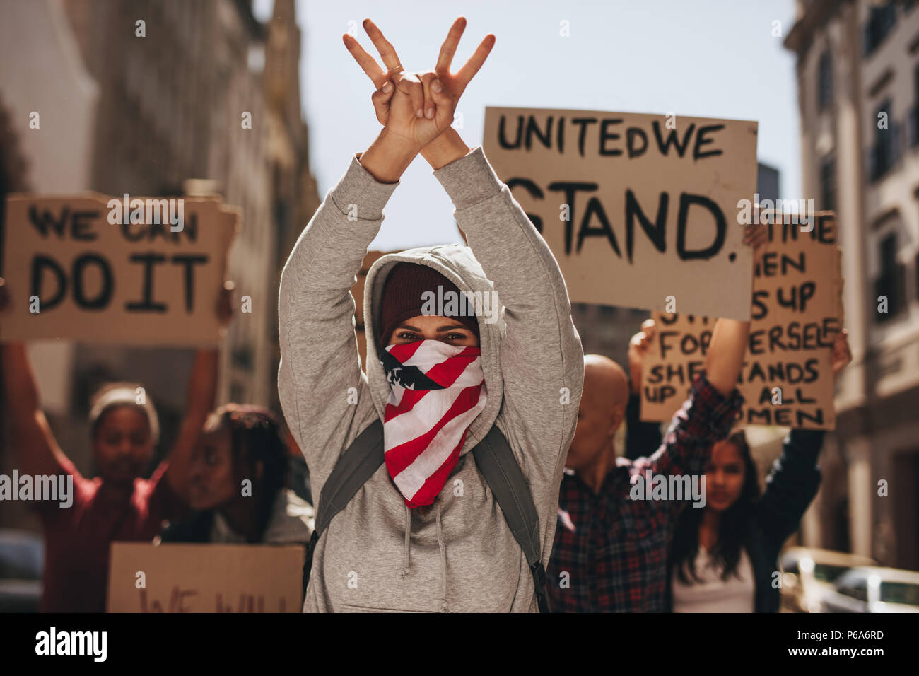 Woman with mouth covered gesturing peace sign with both hands on road. Group of women protesting silently on road. Stock Photo