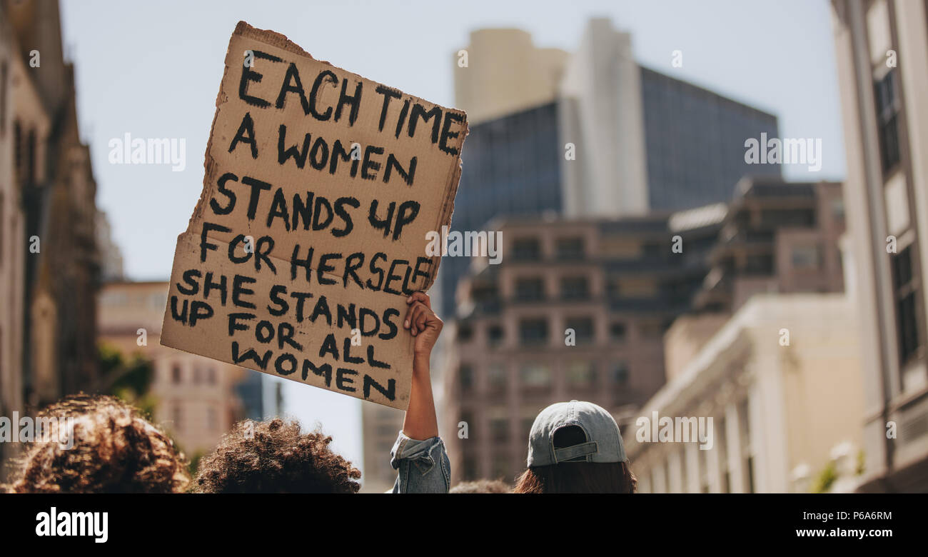Group of demonstrators on road with a signboard saying each time a woman stands up for herself she stands up for all women. Activist demonstrating wom - Stock Image