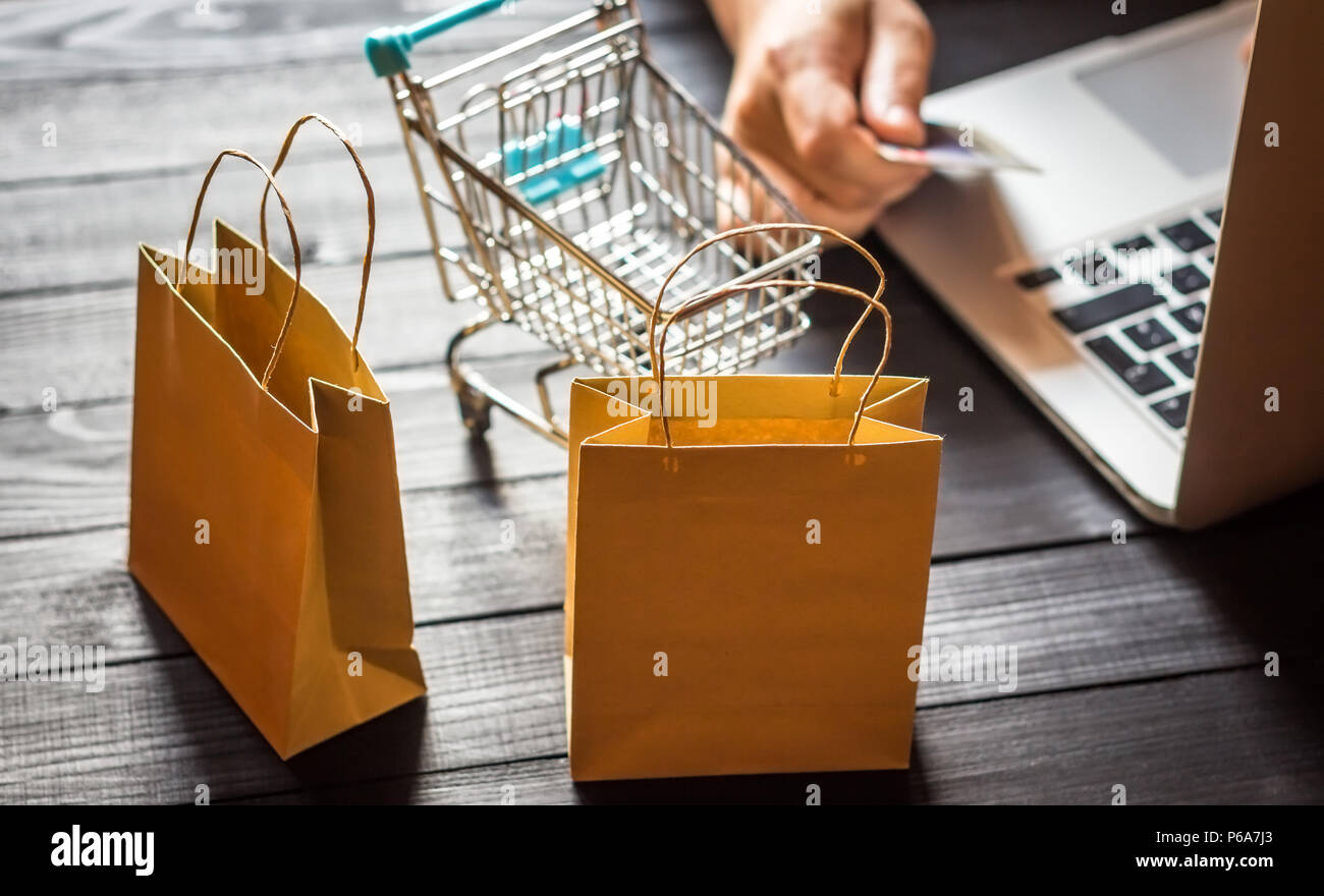 422c48af Online shopping concept, young men using laptop and holding credit card ,  selective focus on shopping bags