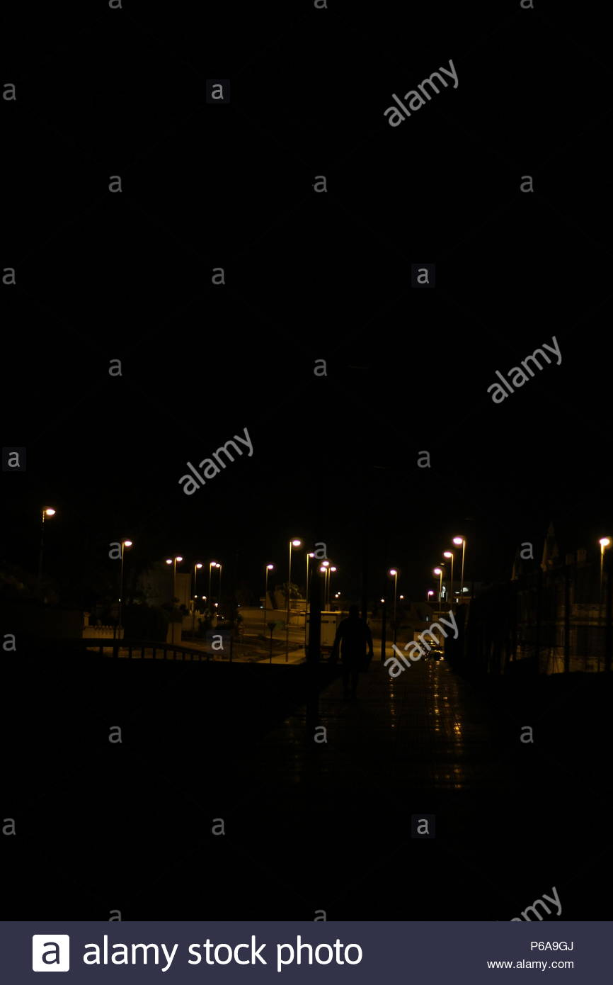 Nocturnes - Strangers- Silhouette of a male figure walking along dark shadowy streets at night. - Stock Image