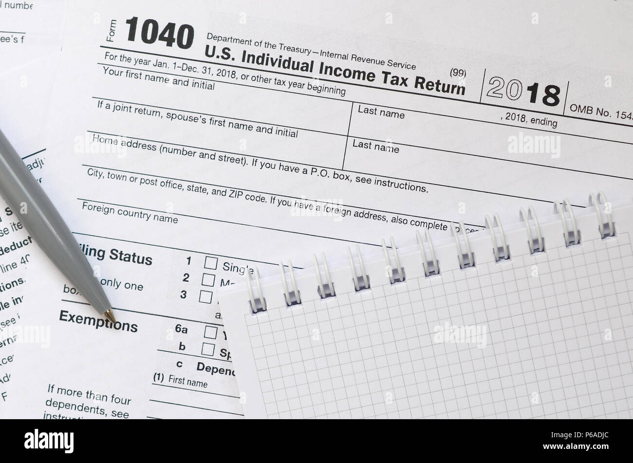 form 1040 us tax  The pen and notebook is lies on the tax form 12 U.S. ...