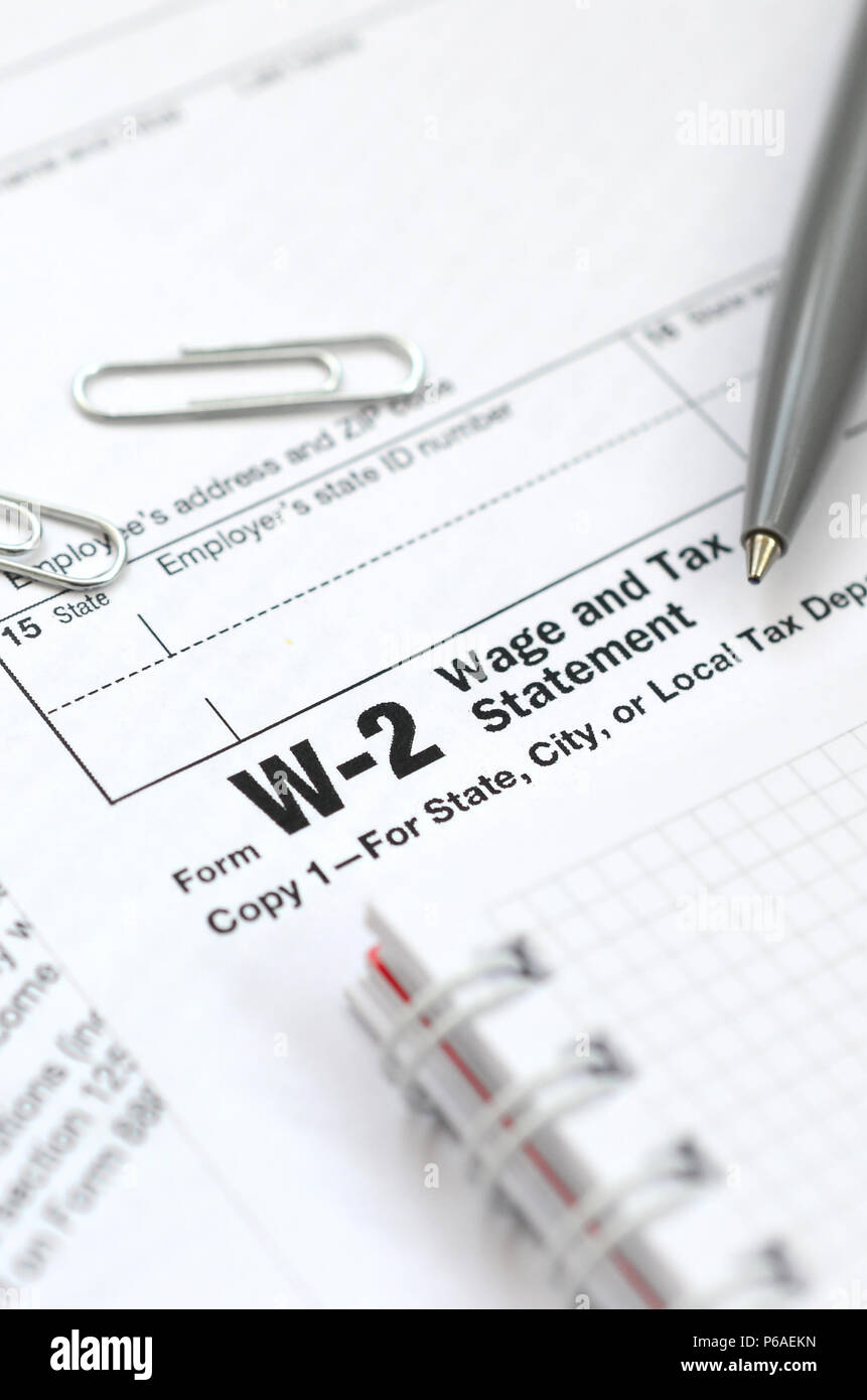 The pen and notebook on the tax form W-2 Wage and Tax Statement. The time to pay taxes . - Stock Image