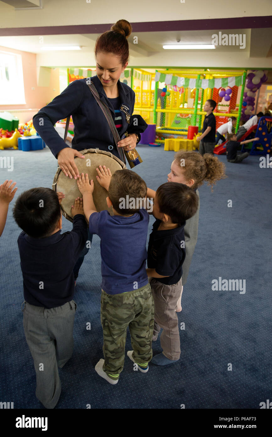 A teacher with Cambridge School of Constanta gets the attention of her students by letting them bang on her drum before transitioning to their next activity, Constanta, Romania, May 25, 2016.  U.S. Marines and Romanian students from Ovidius University of Constanta spend the afternoon reading and interacting with children from Cambridge School of Constanta.  Marines participate in community relations events in order to interact with the local public outside of the military training environment.  (U.S. Marine Corps photo by Cpl. Kelly L. Street, 2D MARDIV Combat Camera/Released) - Stock Image